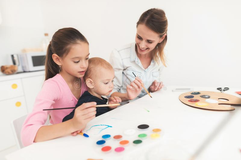 Mother and children are engaged in drawing. They have fun in the kitchen. The girl is holding her younger brother in her royalty free stock photos