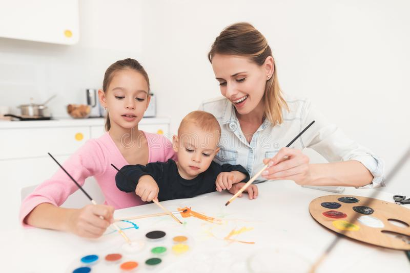 Mother and children are engaged in drawing. They have fun in the kitchen. The girl is holding her younger brother in her royalty free stock images