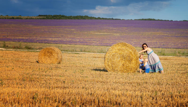 Mother with children on the field with hay royalty free stock image