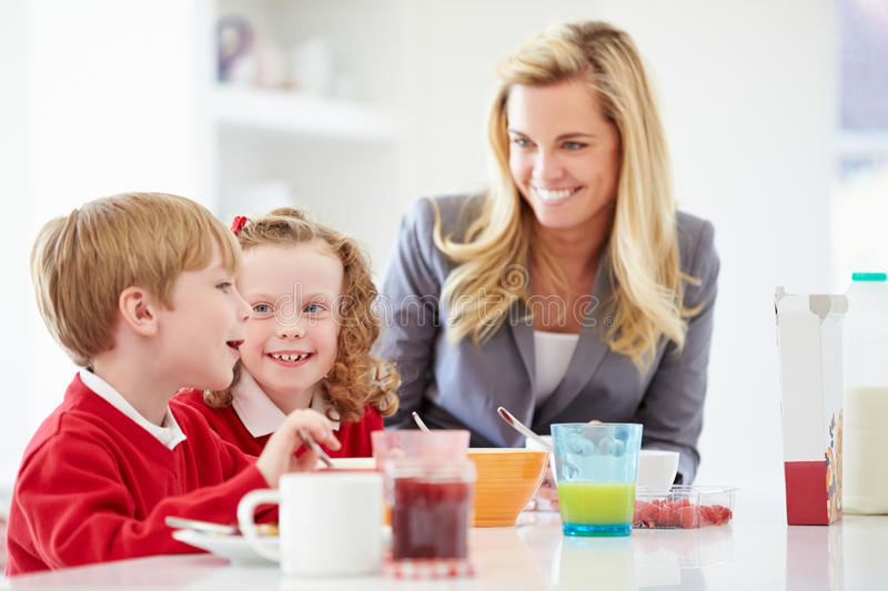 Mother And Children Having Breakfast In Kitchen Together royalty free stock photo