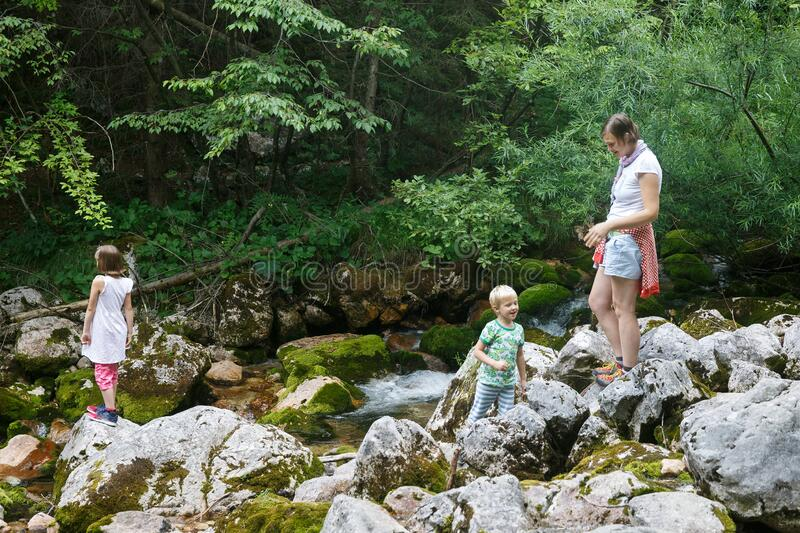 Mother with children having fun, playing by a mountain creek in summer royalty free stock image