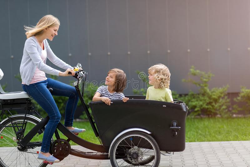 Mother and children having a ride with cargo bike. At sunny day royalty free stock photography