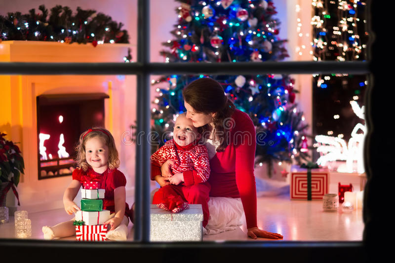 Mother and children at home on Christmas eve. Family on Christmas eve at fireplace. Mother and little kids opening Xmas presents. Children with gift boxes royalty free stock photos