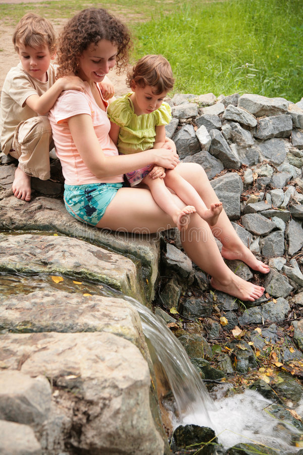 Mother With Children Look At Small Waterfall Royalty Free Stock Images