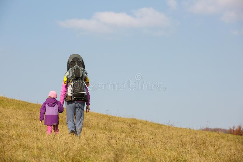 Mother with children hiking on a nice autumn day carrying kid stock photos