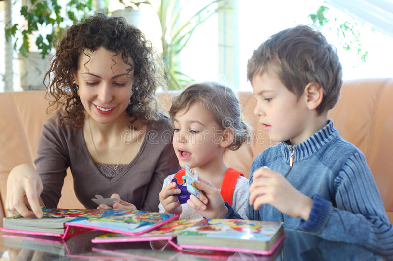 Mother And Children Play With Jigsaw Puzzle Royalty Free Stock Photos