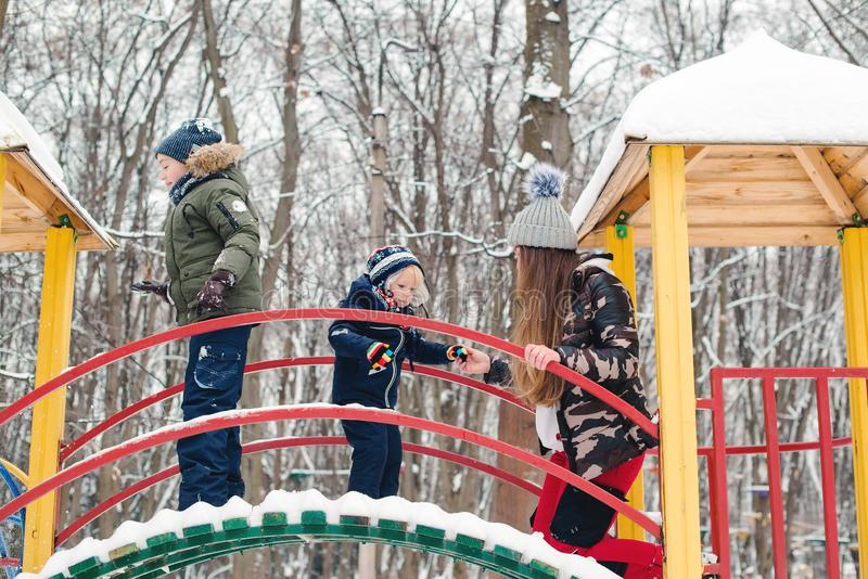 Mother with children at playground in winter park. Happy and healthy childhood stock photography