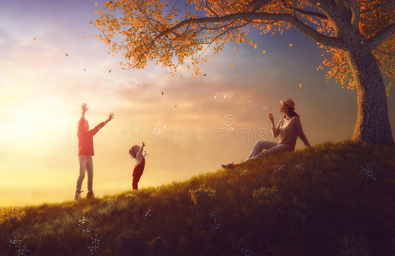 Mother and children playing on autumn walk. Mother and her children girls are playing together on autumn walk in nature outdoors. Happy loving family are having royalty free stock photos