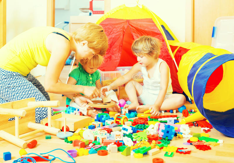 Mother and children playing. With toys in interior royalty free stock image