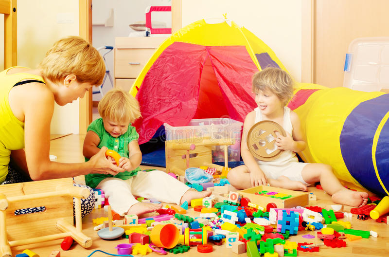 Mother and children playing. Woman and two children together playing with toys in interior royalty free stock photography