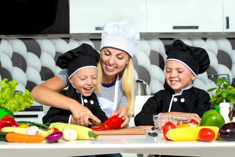 A family of cooks.Healthy eating.Mother and children prepares vegetable salad in kitchen. stock image