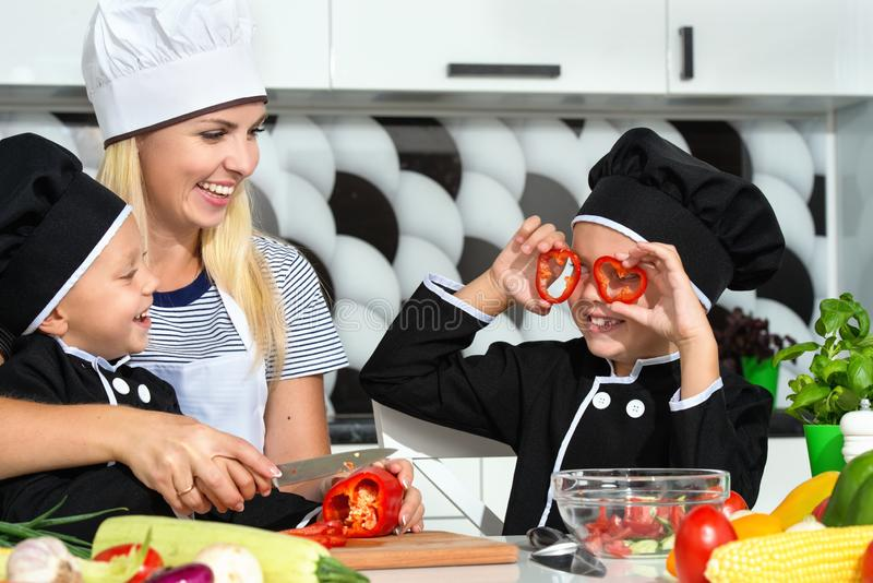 A family of cooks.Healthy eating.Mother and children prepares vegetable salad in kitchen. stock photo