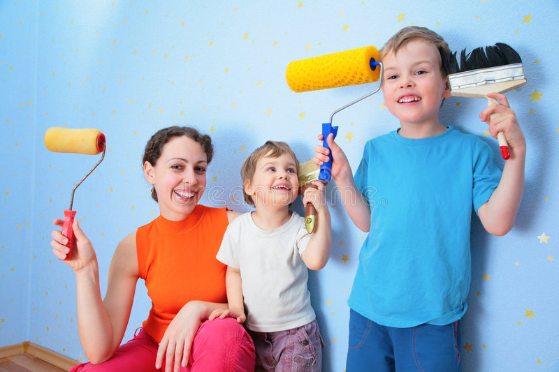 Mother and  children with rollers and brushes