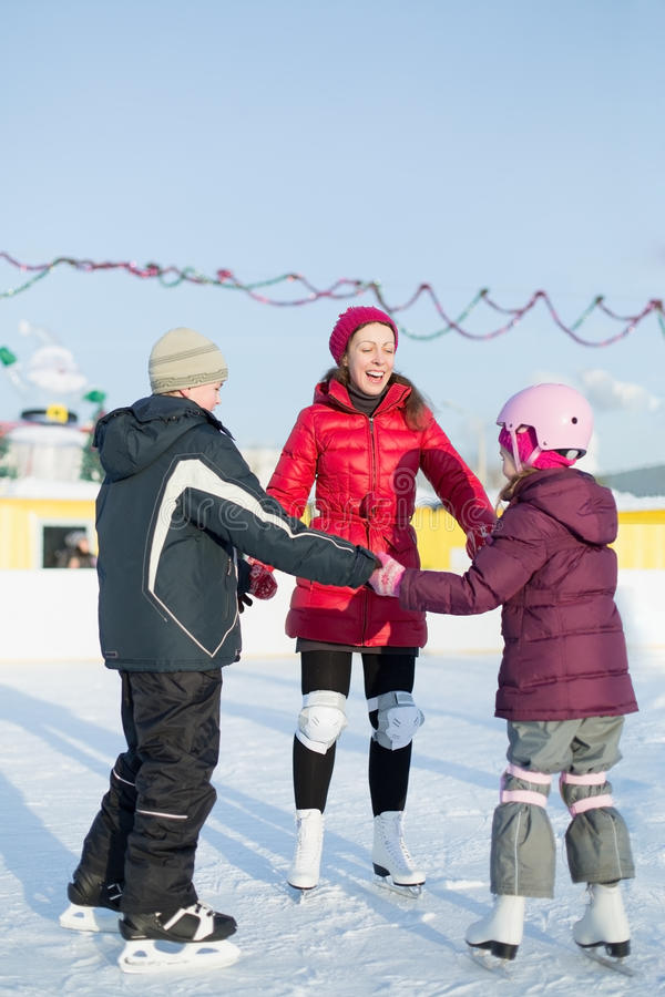A mother with children are skating on outdoor skating rink. A mother with two children are skating on the outdoor skating rink in winter royalty free stock photos