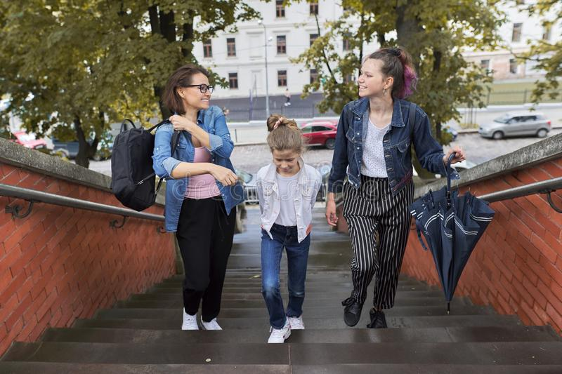 Mother and children two daughters walking on the stairs stock photos