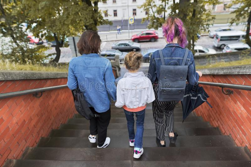 Mother and children two daughters walking on the stairs stock photography