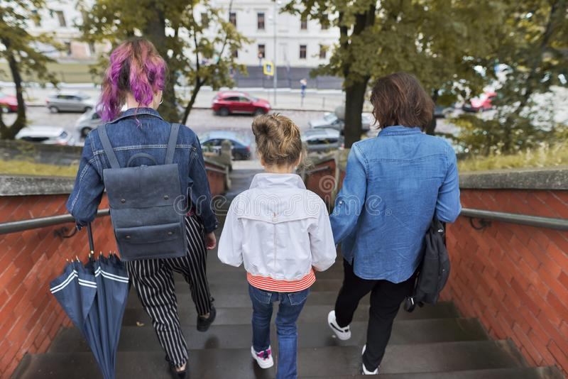 Mother and children two daughters walking on the stairs. In the autumn city, view from the back royalty free stock images