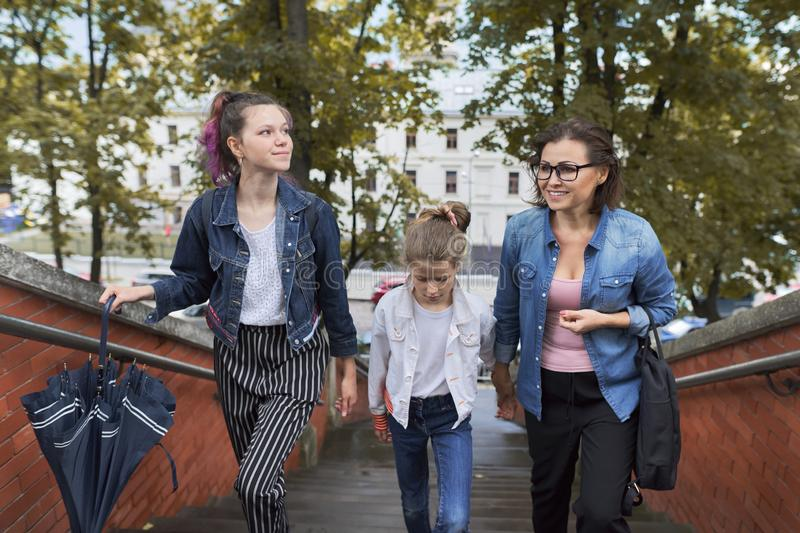 Mother and children two daughters walking on the stairs. In autumn city stock photos