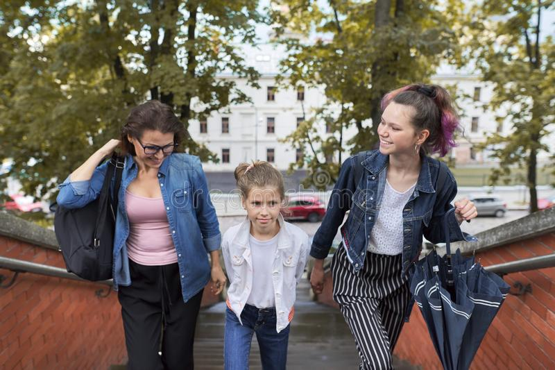Mother and children two daughters walking on the stairs stock image
