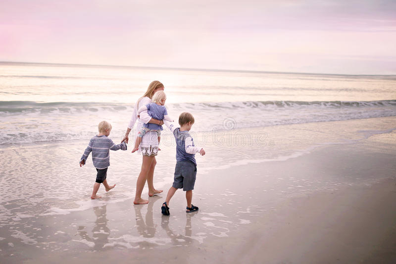 Mother and Children Walking Along Ocean Beach at Sunset stock image