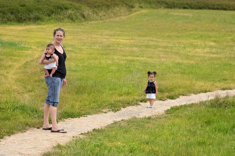 Mother with children walking outdoors. Young single mom family walking on a trail stock photography