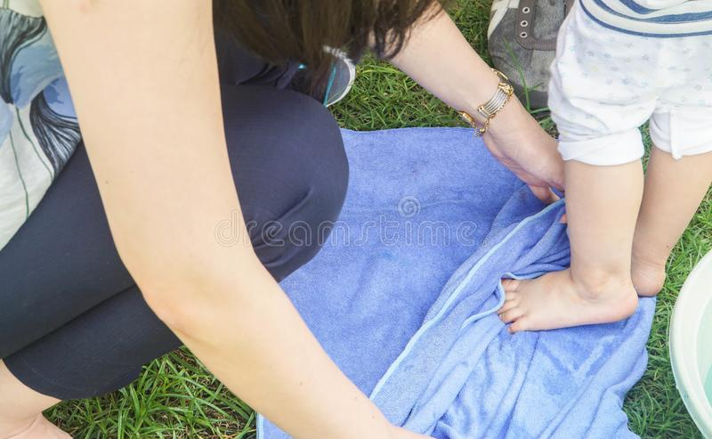 Mother clean and wipe child wet feet. Close up mother clean and wipe child wet feet stock images