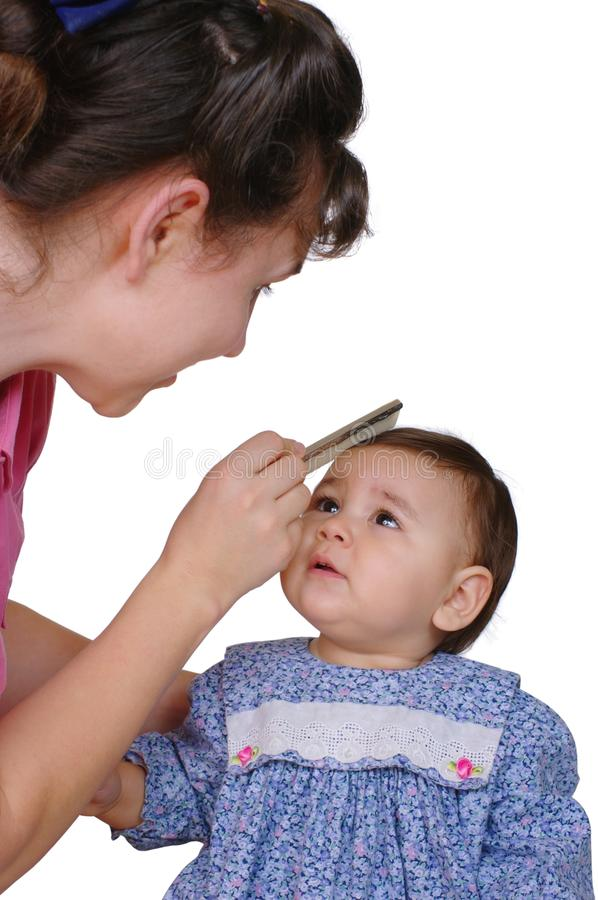 Mother combing baby daughter's hair royalty free stock photography