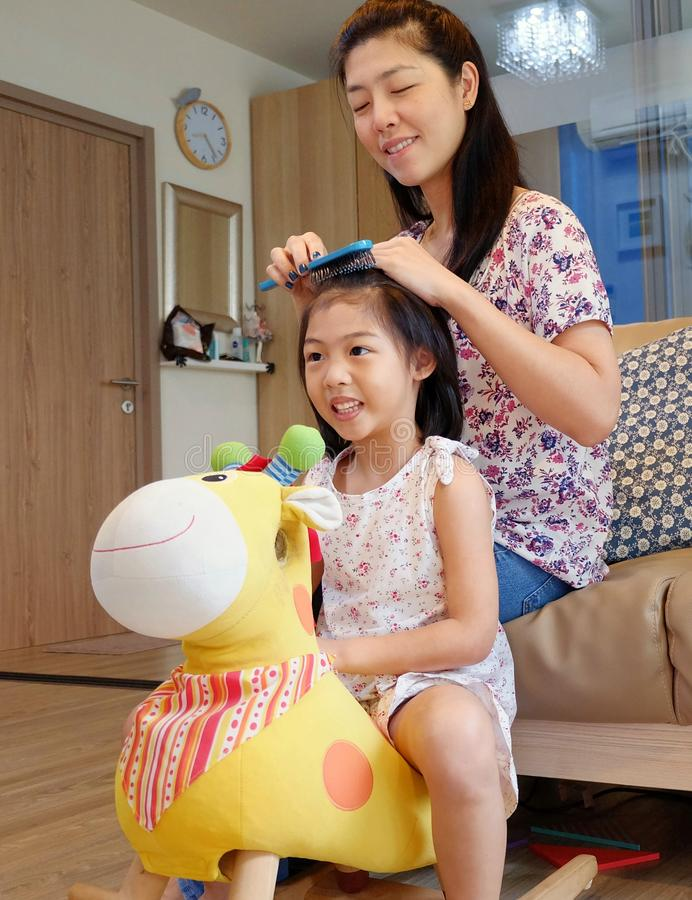 A mother combing her daughter`s hair stock images