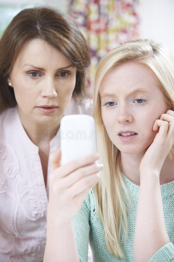 Mother Comforting Daughter Being Bullied By Text Message. Mother Comforting Girl Being Bullied By Text Message royalty free stock photography