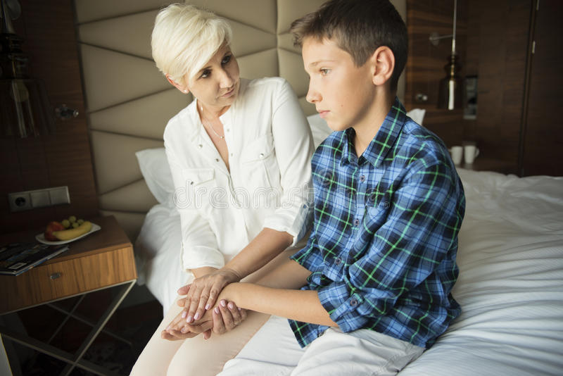 Mother comforting her teenage son royalty free stock images