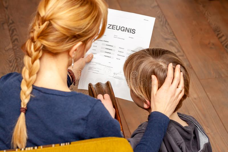Mother comforting son despite the bad school certificate - Translation: certificate day of birth disciplines music. Reading religion german english mathematics royalty free stock photos