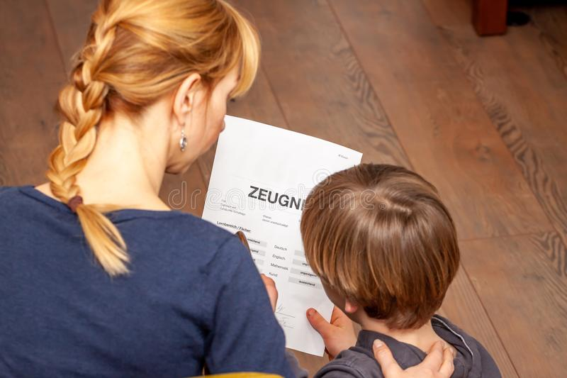Mother comforting son despite the bad school certificate - Translation: certificate day of birth disciplines music. Reading religion german english mathematics royalty free stock photo