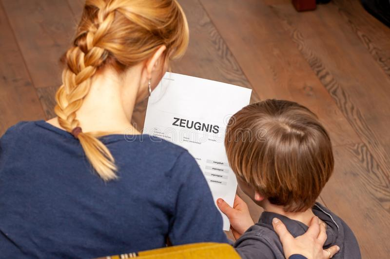 Mother comforting son despite the bad school certificate - Translation: certificate day of birth disciplines music. Reading religion german english mathematics stock images