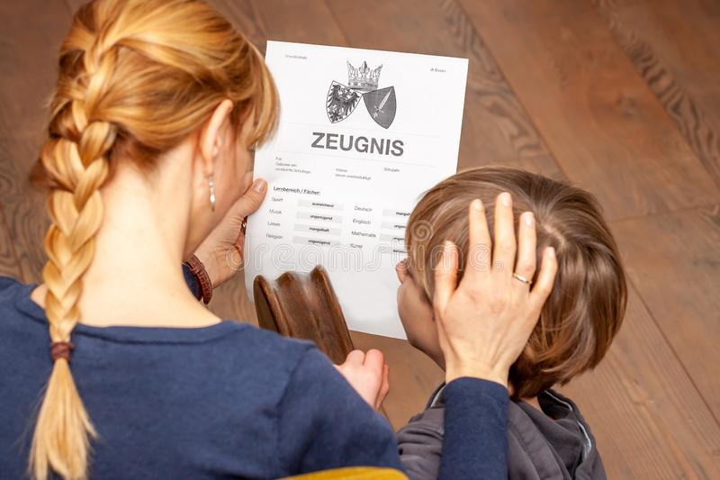 Mother comforting son despite the bad school certificate - Translation: certificate day of birth disciplines music. Reading religion german english mathematics stock image