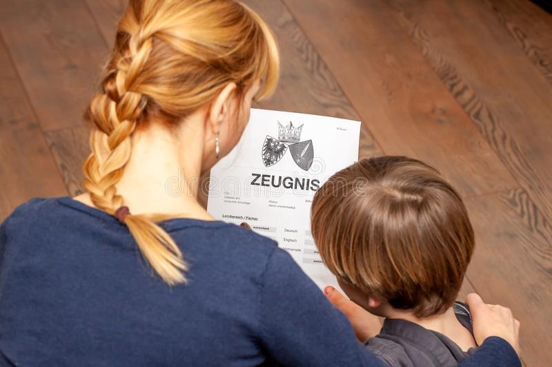 Mother comforting son despite the bad school certificate - Translation: certificate day of birth disciplines music. Reading religion german english mathematics stock photos