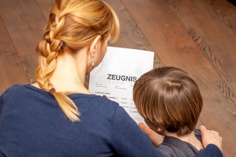 Mother comforting son despite the bad school certificate - Translation: certificate day of birth disciplines music. Reading religion german english mathematics royalty free stock images
