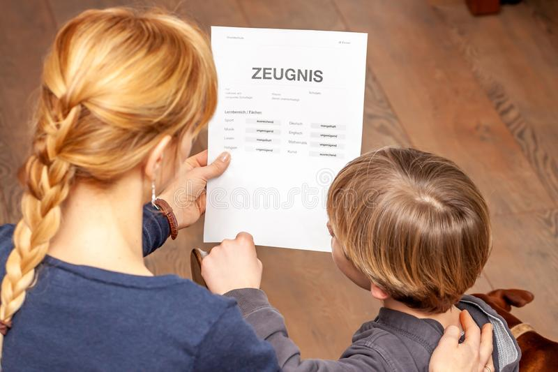 Mother comforting son despite the bad school certificate - Translation: certificate day of birth disciplines music. Reading religion german english mathematics royalty free stock image