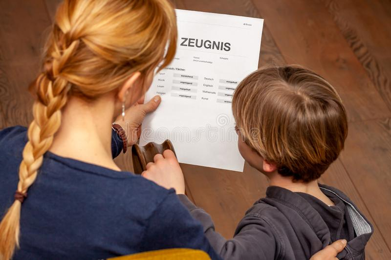 Mother comforting son despite the bad school certificate - Translation: certificate day of birth disciplines music. Reading religion german english mathematics stock photography