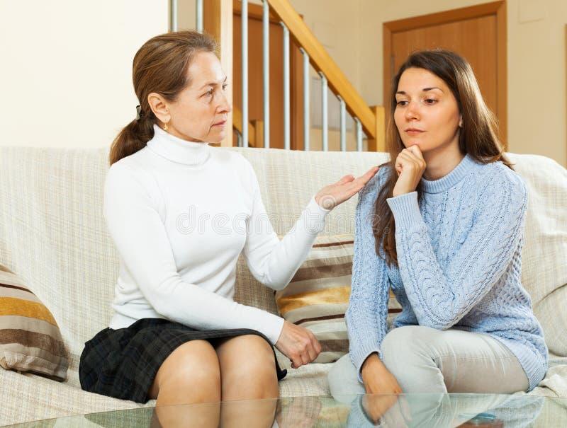 Mother comforting teen. Mature mother comforting sad daughter at home stock photos