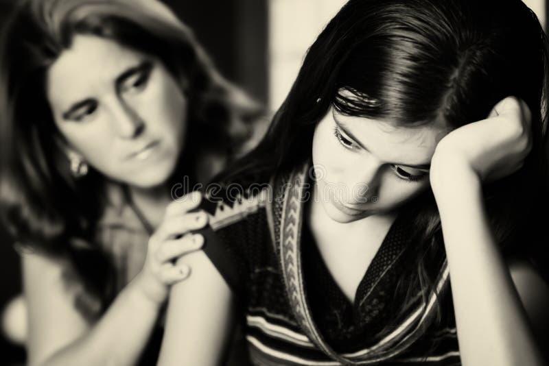 Mother comforts her teen daughter. Teenage problems - Mother comforts her troubled teenage daughter stock images
