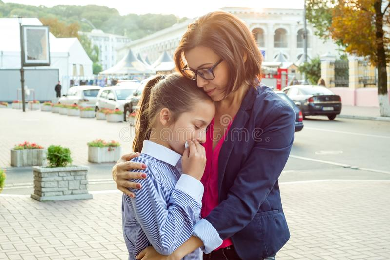 Mother consoling her crying daughter. Urban background. stock photography