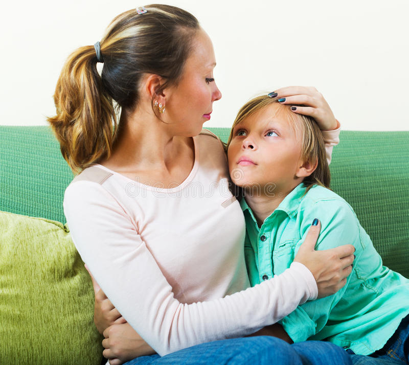 Mother consoling sad teenager at home. Focus on boy stock photos
