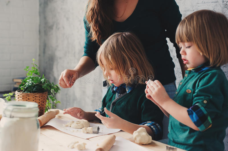 Mother cooking with kids in kitchen. Toddler siblings baking together and playing with pastry at home. In weekend morning royalty free stock image