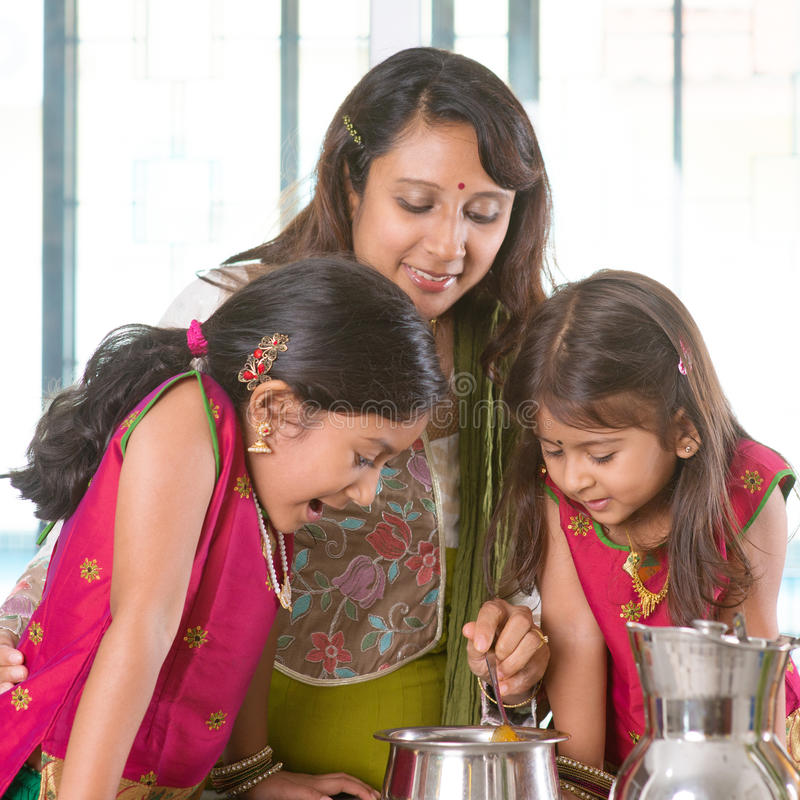 Mother cooking in kitchen. Asian family cooking food together in kitchen. Indian mother and children preparing meal at home. Traditional India people with sari royalty free stock image