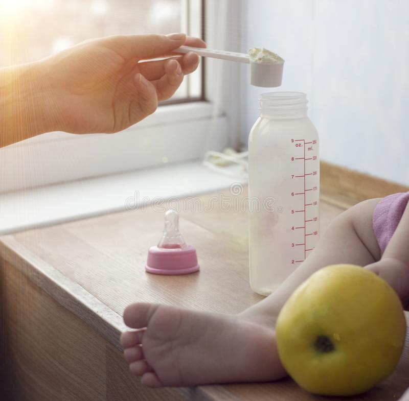 Mother cooks baby food for the child, a close up, a hand and a small bottle stock photo