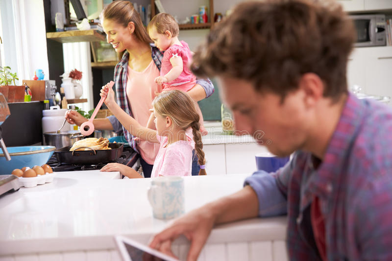 Mother Cooks Family Meal Whilst Father Uses Digital Tablet royalty free stock photography