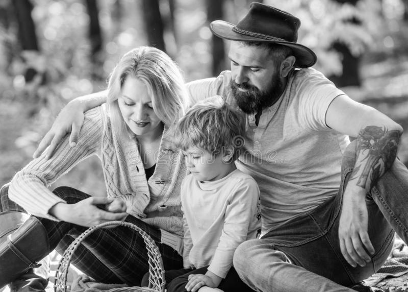 Mother, cowboy father love little boy child. Sunny weather. Healthy food. Spring mood. Happy family day. Family picnic. Happy son with parents relax in autumn royalty free stock photography