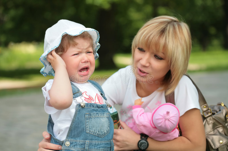 Mother and crying little daughter stock images