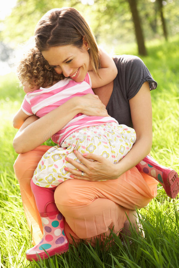 Mother Cuddling Young Daughter In Summer Field stock images