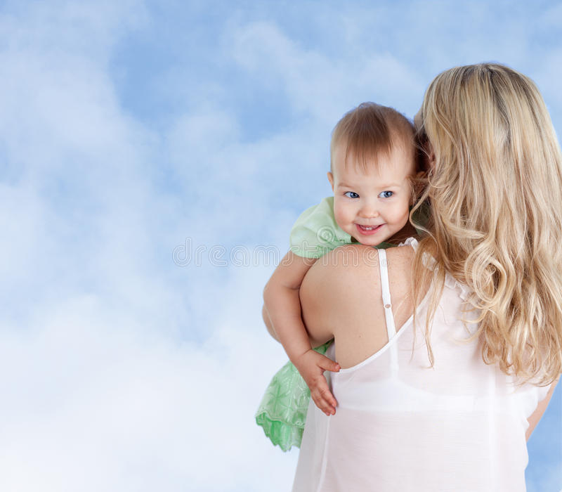 Mother with cute baby girl looking over shoulder stock photo